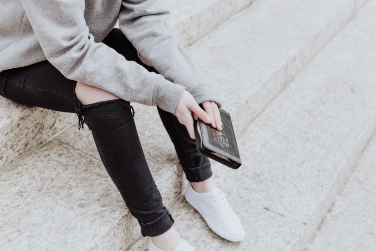 Young person holding a Bible