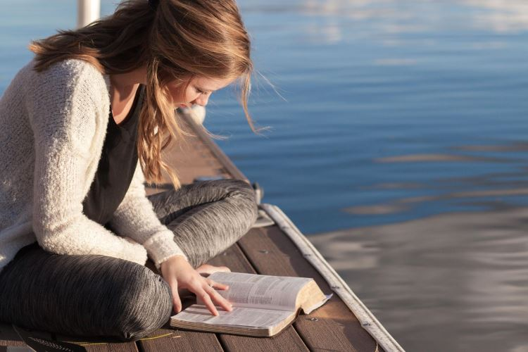 Young women reading the Bible by the ocean