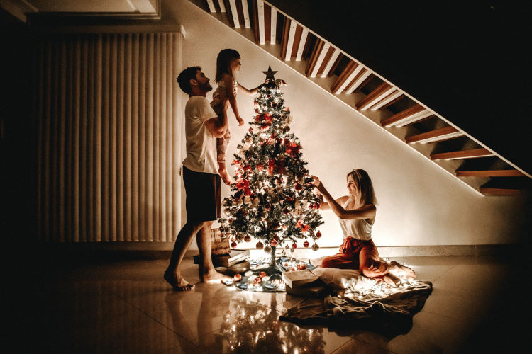 Young family setting up the Christmas tree at night