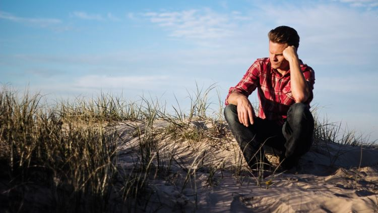 Man looking depressed and sad on the beach