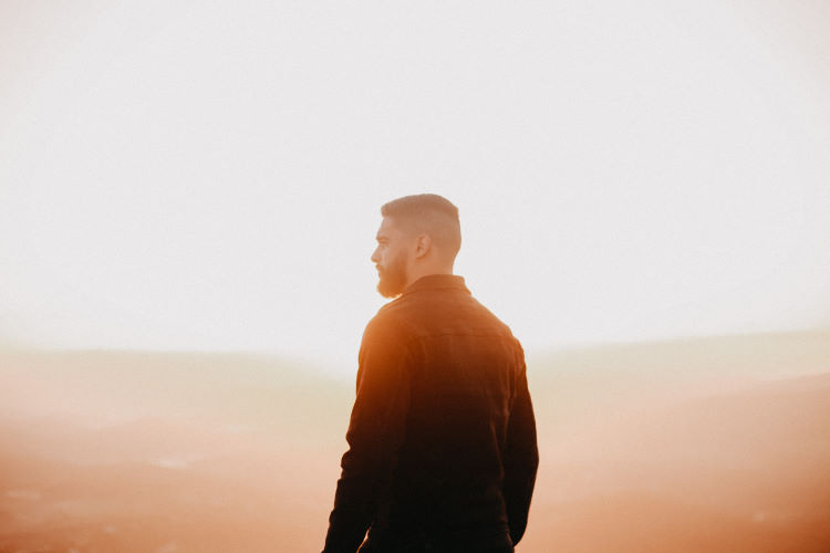 Man with beard looking to left with sun shining behind him