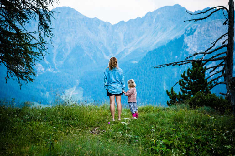 A mother and daught hold hands looking off into the distance at a mountain.