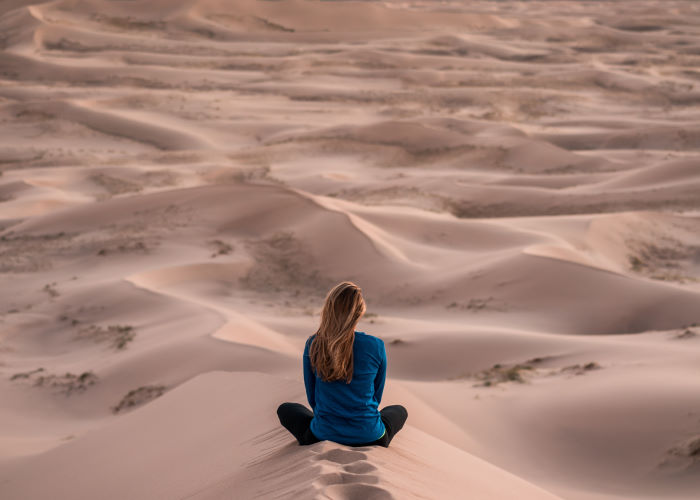 Women sitting in sand with her back to the camera, looking at the view.