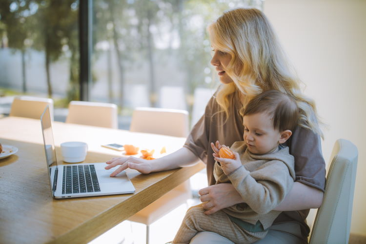 Young mother with toddler sitting on your lap while she looks at her laptop