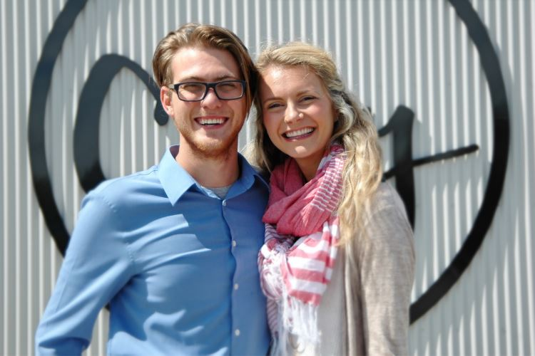 Couple smiling in front of the City Church sign