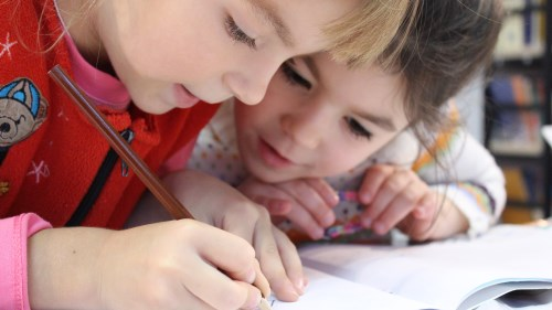 Two children learning and writing together