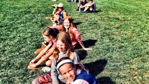 Primary students sitting on grassy field talking and smiling