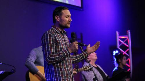 Pastor Garth Chin Poy standing on stage praying
