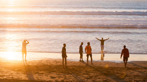 Friends standing together on a beach at sunset