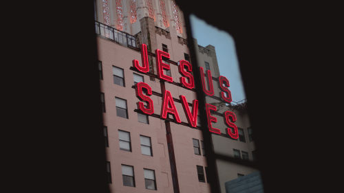 A building with a sign that reads 'Jesus Saves' on it