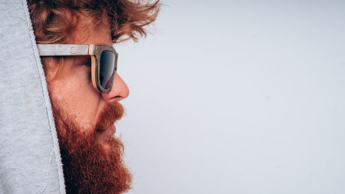 A side profile of a bearded man wearing a hoodie and sunglasses