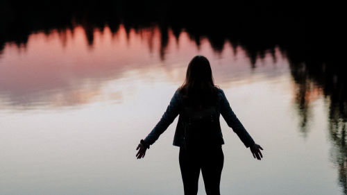 A woman with arms outstretched standing in before a lake at sunset praying to God